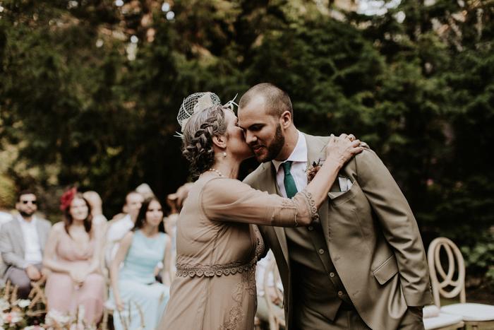 madre del novio besando al aire libre