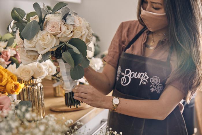 persona en el delantal de The Bouqs Co trabajando en las flores